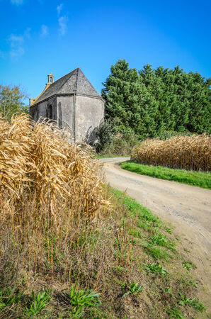 Small old medieval building in dry ripe corn field with curved road, France, Brittany