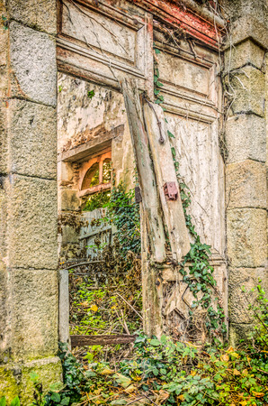 Broken door and old abandoned house with plants growing inside, France, Brittany Banque d'images