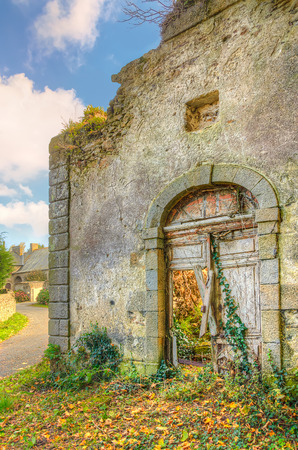 Old medieval abandoned house in a village with broken door and plants groving inside, France, Brittany Banque d'images