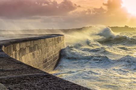 olas de mar: Grandes olas de trituración en curva muelle de piedra, en tiempo tormentoso con puesta del sol viva, marea grande, Saint Malo, Francia.