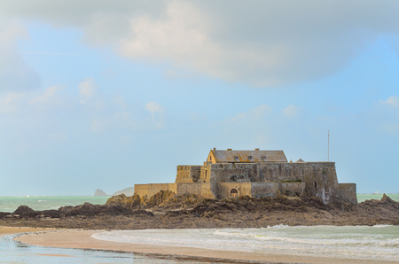 Fort National fortress in St-Malo, France, on windy weather and high tide, with greenish water reflections and waves.