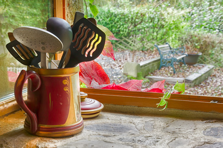 Vintage kitchen window, old pot with utensils, foliage red and orange leaves at early autumn. Focus on red leaves.