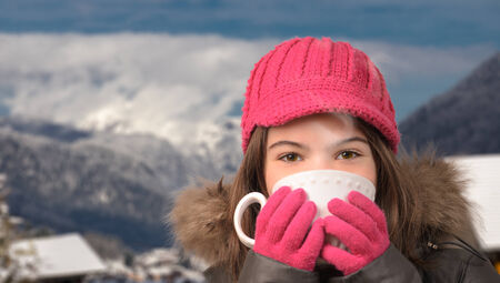 Cute girl with a cup of tea in the snowy mountain village, smoke, vapor, from hot tea with mountain peak in the distaance, pretty brown eyes.