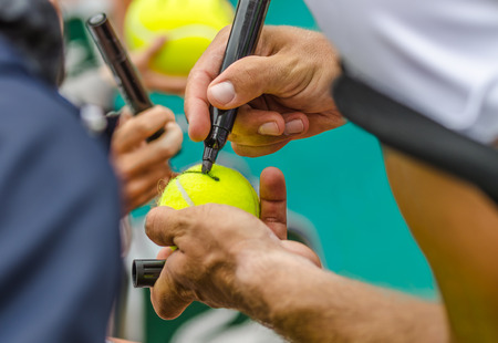 Tennis joueur signe autographe sur une balle de tennis après la victoire, photo de plan rapproché montrant balle de tennis et les mains de la signature d'un homme faisant, l'Open d'Australie, l'US Open. Banque d'images - 35536324