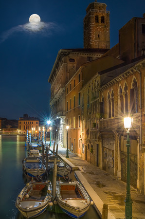 canal street: Anchored boats in Venice canal, street lit by lamps and full moon, with moving clouds, green water reflection Stock Photo