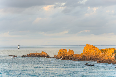Cliffs with lighthouse in distance, with rocks illuminated by last sun rays before sunset, Brittany, France Banque d'images