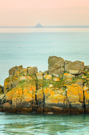Yellow rocks on French coast with silhouette of Mont Saint Michel in the distance with warm sky from sunset, Saint-Malo, France