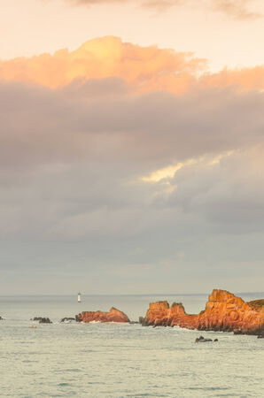 Cliffs under big cloudy sky with lighthouse in distance, rocks illuminated by last sun rays before sunset, sunlight, Saint Malo, Brittany, France Banque d'images