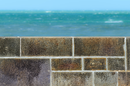 Stone fence wall and greenish turquoise sea in the distance