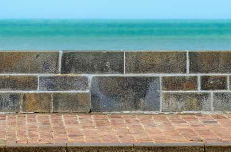 Stone fence wall and tiled pavement next to the  turquoise sea