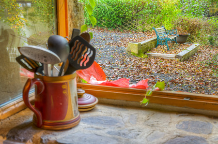 Bench in the garden seen through old kitchen window with foliage red and orange leaves at early autumn. Kitchen utensils at the window.