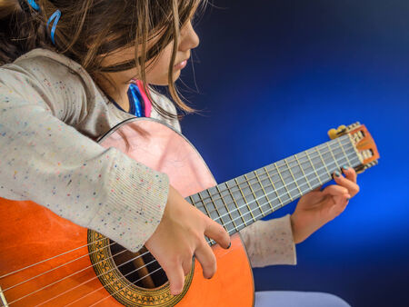 Little girl plays red shiny classical guitar, blue light, performance, concert, focus on right hand. Banque d'images