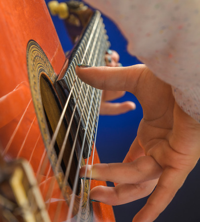 Girl hand closeup playing red classical gutar in a blue light, focus on right hand fingers.