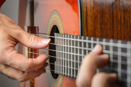 Man hands closeup playing red classical gutar, focus on right hand fingers with nails in a position. Banque d'images