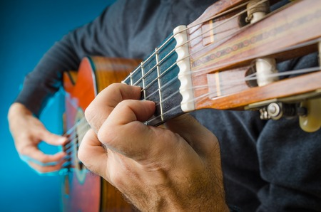 Closeup of a Man playing red classical gutar on concert, with fingers, focus on left hand position.
