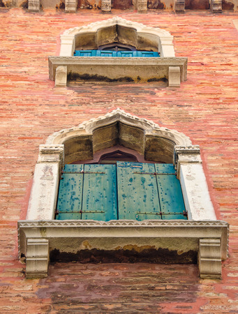 Old, medieval arched windows with blue and green shutters in Venice, Italy, perspective, low angle view.