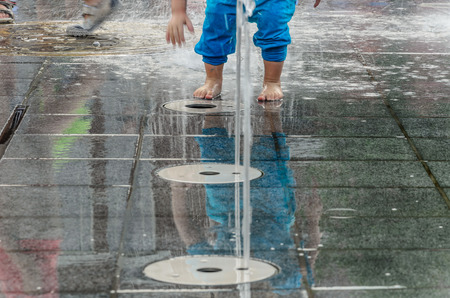 Kids playing in fountain with waterspouts comming from underneath happy and curious Banque d'images