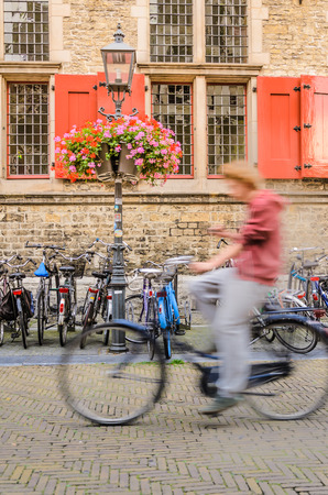 Delft market square bicycle rider in motion blur next to Delft city hall Netherlands