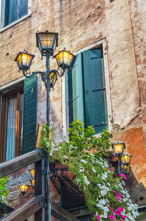 Old building facade green shutters and flowers in shadow lamps with lights on Venice Italy.