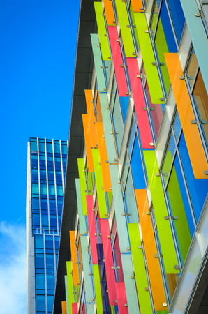 Modern building with multicolored windows and design panels attached in Amsterdam Netherlands vertical position Banque d'images
