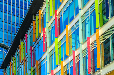 horizontal position: Modern building with multicolored windows and design panels attached in Amsterdam Netherlands horizontal position. Stock Photo