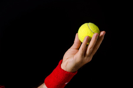 to toss: Closeup of man hand, arm, preparing to toss the tennis ball, performing the serve. Preparation for serve. Tennis player, competition. Isolated on black.