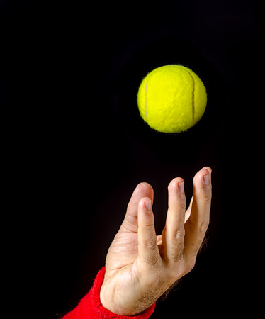 Closeup of man hand, arm, tossing the tennis ball, performing the serve. Tennis serve. Player on  competition. Isolated on black. Ball captured in the air. Left hand.