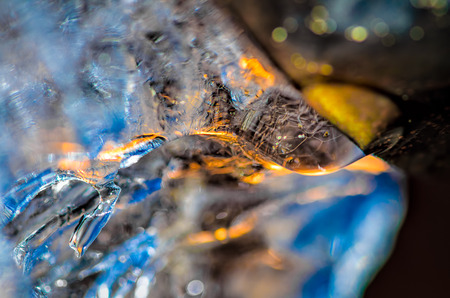 Drop of melting ice water at the drainpipe, with reflections of blue sky and yellow sun rays passing through. Macro with ice structure seen through the drop of water.
