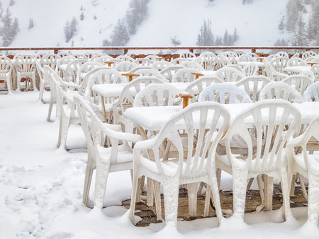 Rows of chairs in empty outdoor restaurant covered with snow snowy winter cold weather on a mountain.