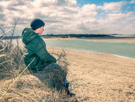 Little boy  sitting at the dune, looking the high tide coming, north sea, Dutch coast near Cadzand. Vintage filter used.