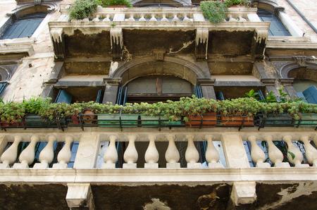 façade de l'immeuble vieux avec grand balcon, des fleurs et des arcs, tourné sous le balcon, Venise, Italie.