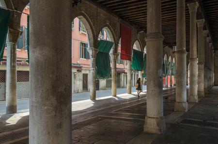 Un grand bâtiment avec des piliers et des arcs, et une femme en passant par la distance, Venise, Italie.
