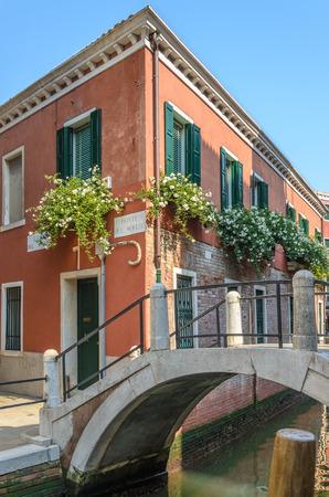 Ancien bâtiment rouge et un petit pont, des fleurs et des arcs, Venise, Italie.