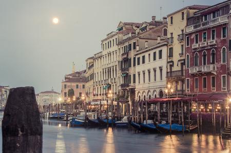 télécabines préenregistrées et bâtiments anciens accross Grand canal, à côté du pont du Rialto, le lever du soleil à Venise, en Italie, avec la pleine lune