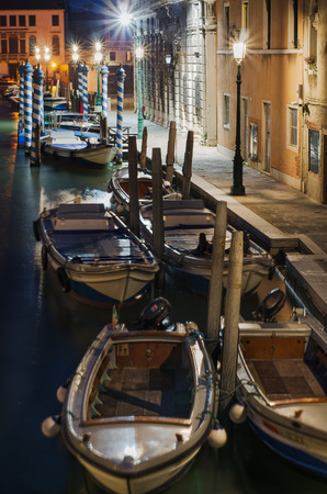 Anchored boats in Venice canal, empty street lit by lamps, view froma bridge.