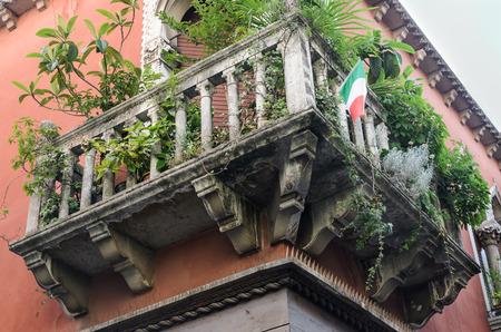 façade de l'immeuble vieux avec grand balcon, des fleurs, des plantes et des arcs, tourné sous le balcon, avec le drapeau italien, Venise, Italie.