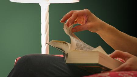 Main de femme tenant et tournant une page d'un livre, sous la lumière de la lampe, avec fond vert.