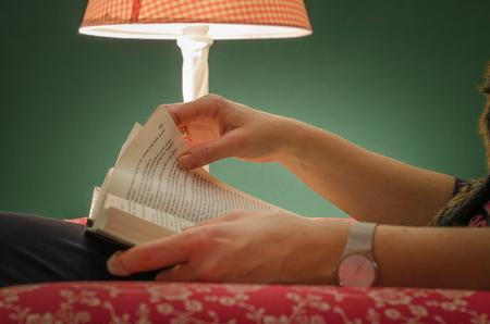 Main de femme tenant et tournant une page d'un livre, sous la lumière de la lampe rose, avec fond vert. Banque d'images - 85657388