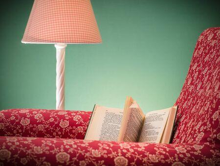 Livre ouvert sur le fauteuil rouge reste gauche après lecture, avec fond vert et lampe rose, Une page rabattue (oreilles de chien) pour marquer la page actuelle. Banque d'images - 85763977