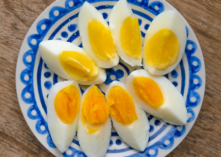 Deux couleurs de jaune, oeufs durs tranchés dans une assiette décorée bleu sur la table de cuisine en bois. Un jaune d'?uf avec un collor jaune, l'autre orange. Banque d'images - 86674016