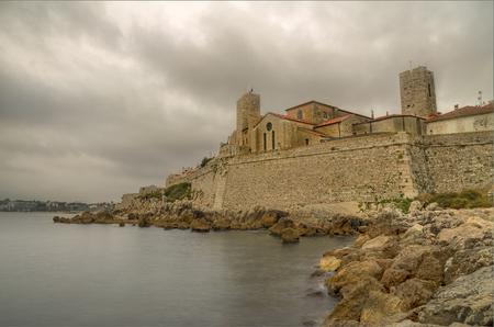 Le panorama de la vieille ville d'Antibes, au début du matin nuageux, vu des rochers à la plage. Banque d'images - 92598203