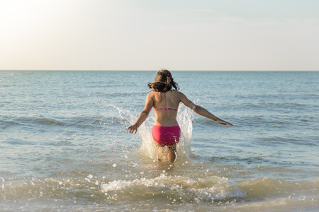 Little pretty girl running to the sea, jumping in the water. Sunny beach in the nord sea. Banque d'images - 86955305