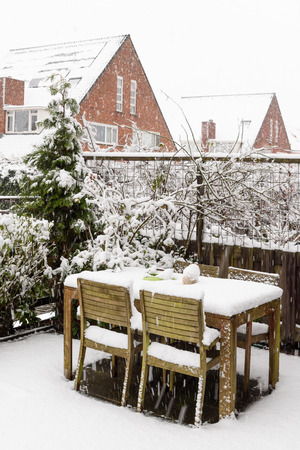 Garden backyard wooden table and chairs under snow Banque d'images - 95339739