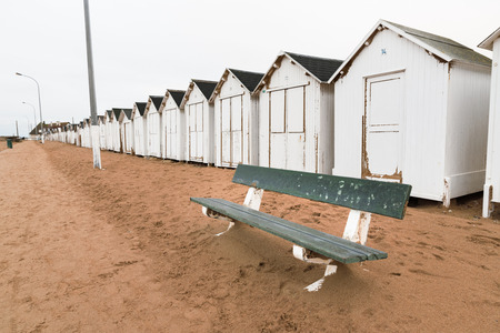 A bench and white bathing beach houses, cabins in a row on the beach Banque d'images - 95286625