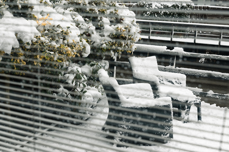 Backyard, garden furniture seen through the door, window with horizontal blinds, jalousie, from inside, outside chairs under snow. Banque d'images - 95334681