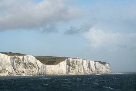 The white cliffs of Dover, lit by sun passing through clouds, view  from the sea, waves from strong wind still present after hurricane Ophelia. Banque d'images - 97290287