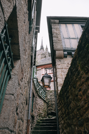 Stairs in a narrow street with stone houses and vintage lamp in Mont Saint Michel village center, in Normandy , France Banque d'images - 97301037