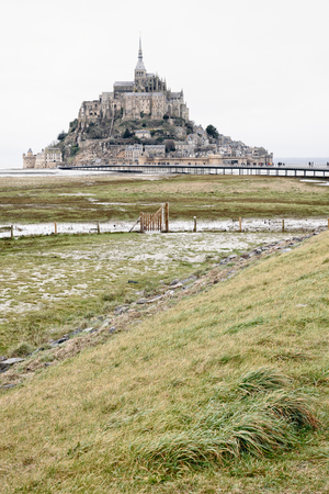 Mont Saint Michele abbey on the top, in a distance with green grass hay in foreground, in a cloudy gray autumn day, France Banque d'images - 97290304