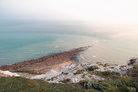 A view from the cliff to the sea, with small beach and setting sun, sunset n Eastbourne, Britain Banque d'images - 101953617