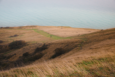 A view from the top of the hill to the sea and cliffs in England with people walking and mountainbike, Eastbourne, Britain Banque d'images - 101807470
